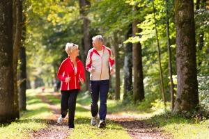 Seniors jogging exercise on forest woods road